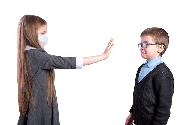 Het meisje met het masker vraagt om afstand te houden van de jongen zonder het masker. geïsoleerd op een witte achtergrond. hoge kwaliteit foto