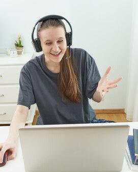 Het meisje met hoofdtelefoons bekijkt met verrassing informatie over computer.