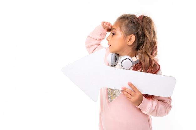 Het meisje met hoofdtelefoons op haar hals houdt een pijl van groot document met een lay-out en kijkt aan de kant op een witte achtergrond