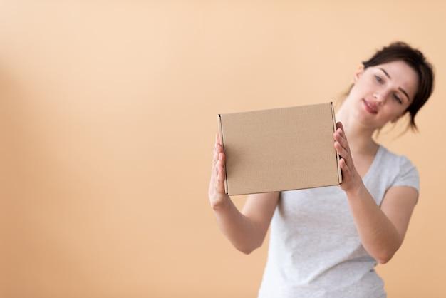 Het meisje met interesse onderzoekt de doos vanaf de zijkant op een beige achtergrond.