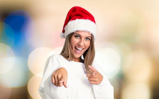 Het meisje met kerstmishoed richt vinger op u over ongericht achtergrond