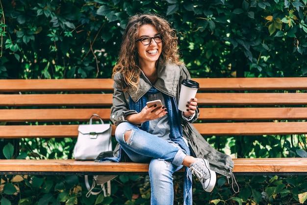 Het meisje met krullend haar drinkt koffie en gebruikt smartphone openlucht