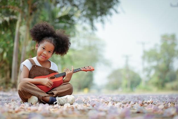 Het meisje met krullend haar geniet van het spelen van de ukelele tijdens het bloeiseizoen