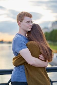 Het meisje met lang dik donker hoort omhelzend roodharigejongen op brug, tienerliefde