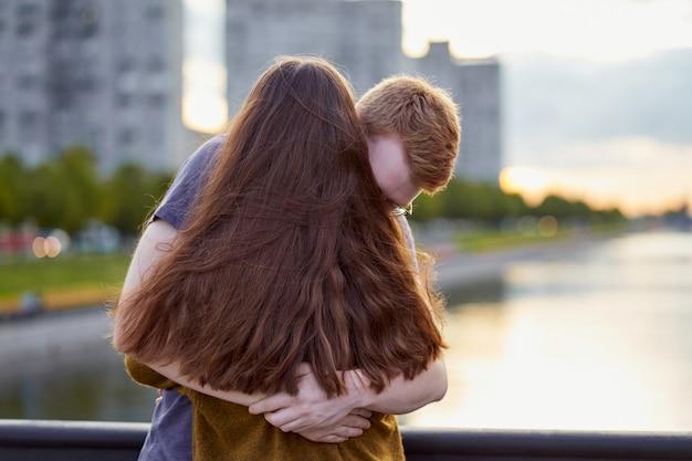 Het meisje met lange dikke dark hoort omhelzende roodharigejongen op brug, tienerliefde bij de zonsondergang