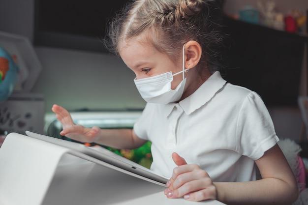Het meisje met medisch masker op haar gezicht concentreerde zich op haar taak met tablet