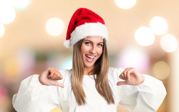 Het meisje met trots en zelf-tevreden kerstmishoed over ongericht achtergrond