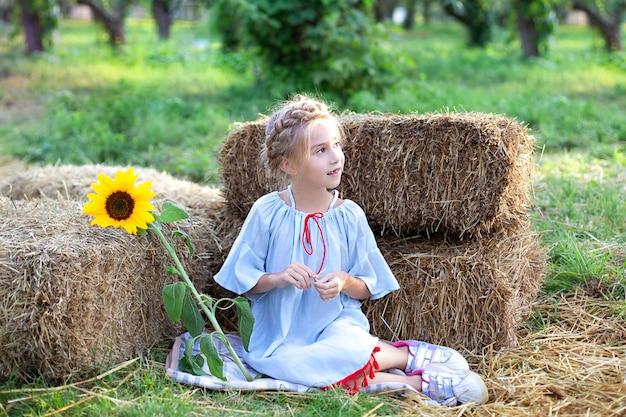 Het meisje met vlecht op haar hoofd zit op rol van hooibergen in tuin en houdt zonnebloem. portret jonge blonde meisje met zonnebloem