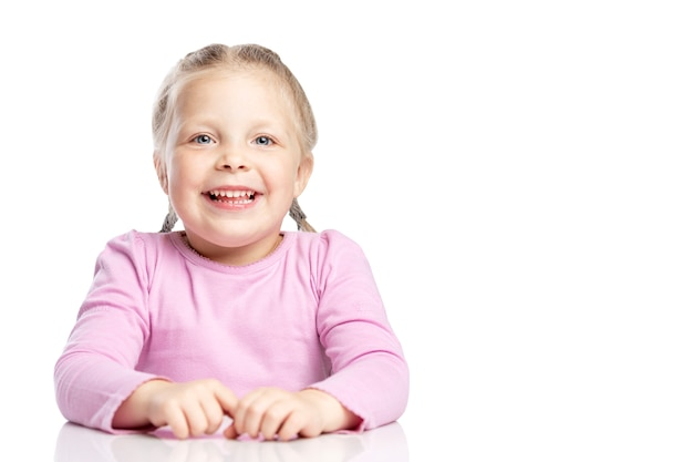 Het meisje met vlechten in een roze sweater lacht.