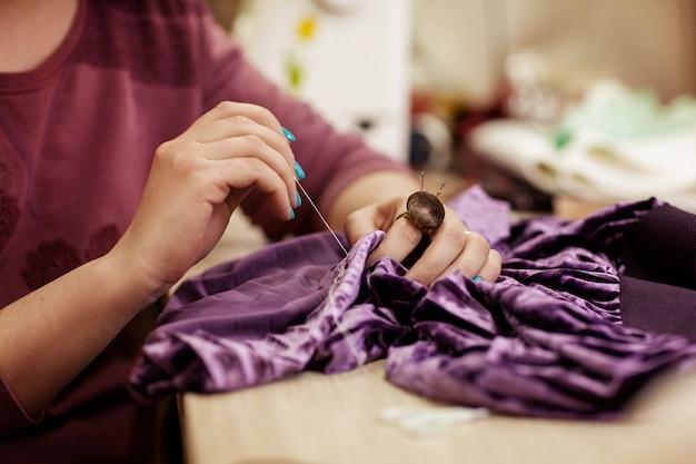 Het meisje naait een jurk, handen van dichtbij