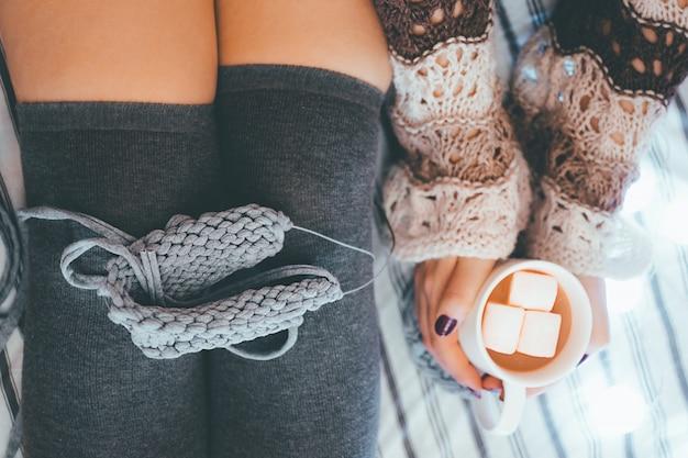 Het meisje naait en houdt koffie met marsmallows