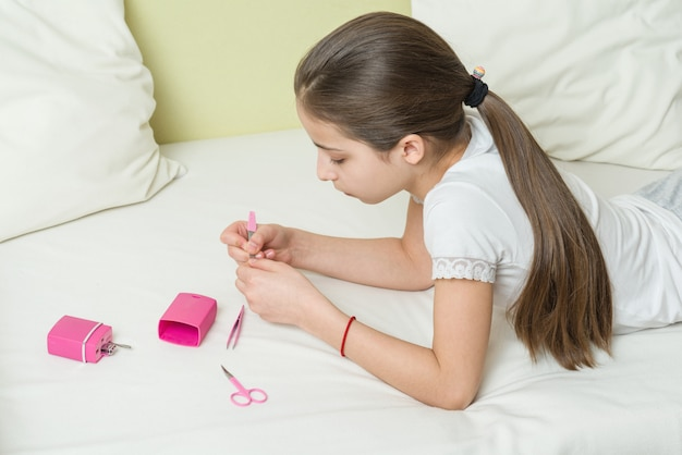Het meisje nagelt thuis haar nagels met behulp van manicure-accessoires