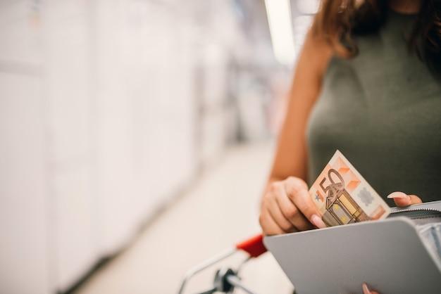 Het meisje neemt een bankbiljet van vijftig euro van portefeuille. detailopname.