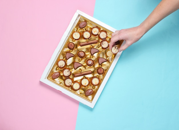 Het meisje neemt een chocoladesuikergoed uit een doos chocolaatjes met een gouden dienblad op blauw roze pastel achtergrond. bovenaanzicht, minimalisme
