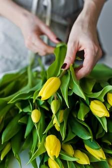 Het meisje neemt een gele tulp, een bos bloemen.