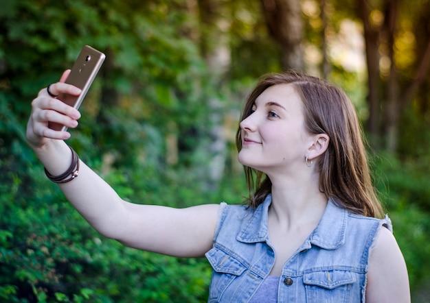 Het meisje neemt een selfie aan de telefoon.