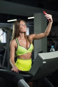 Het meisje neemt een selfie in de gymnastiek, wordt de vrouw gefotografeerd op de tredmolen