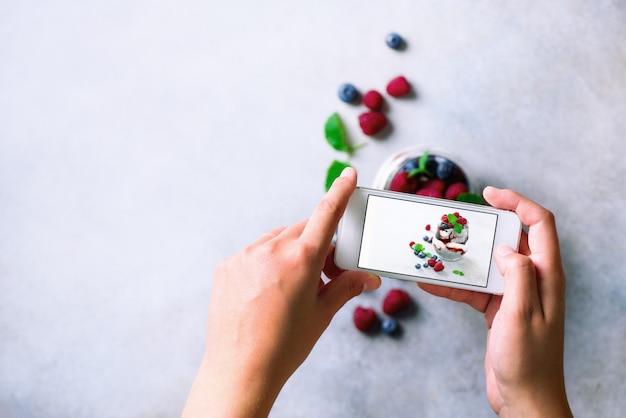 Het meisje neemt foto's van ontbijt, chia pudding met bessen aan mobiele telefoon.