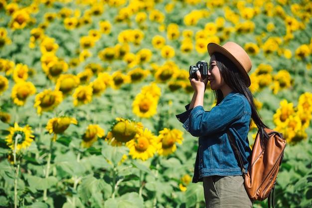 Het meisje neemt graag foto's in het zonnebloemveld.