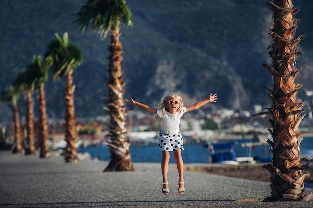 Het meisje nestelt zich en speelt in de natuur, tegen de achtergrond van bergen en palmbomen.