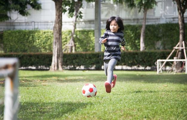Het meisje oefent voetbal als jongen op park