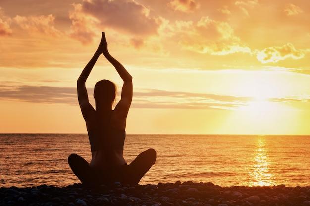 Het meisje oefent yoga op het strand uit. uitzicht vanaf de achterkant, zonsondergang, silhouetten