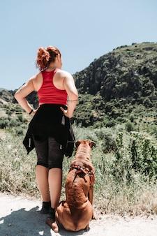 Het meisje onderzoekt sierra nevada in de zomer met een hond