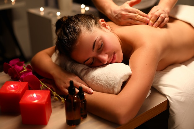 Het meisje ontspande het liggen massage, dichtbij kaarsen en olie