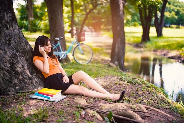 Het meisje ontspant onder de boom in het park met hoofdtelefoons