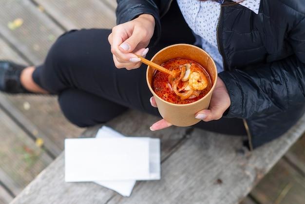 Het meisje op de bank eet soep met zeevruchtengarnalen.