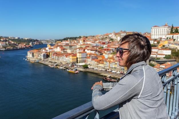 Het meisje op de brug van san luis in de portugese stad porto. kijkt naar het landschap.