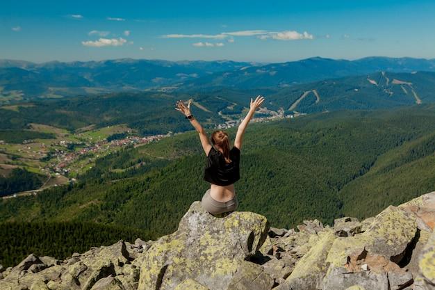 Het meisje op de top van de berg stak haar handen omhoog. brede zomer uitzicht op de bergen bij zonsopgang en verre bergketen bedekt. schoonheid van de natuur