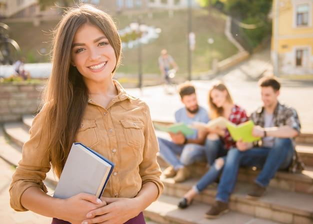 Het meisje op de voorgrond staat en lacht.
