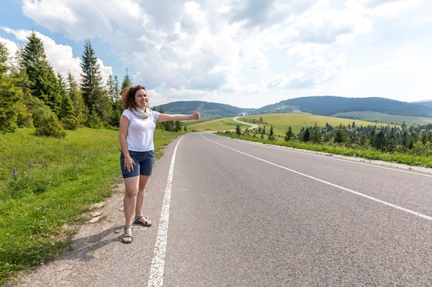 Het meisje op de weg in de bergen vangt een passerende auto liften