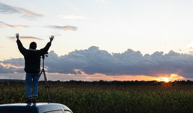 Het meisje op het dak van de auto fotografeert de zonsondergang met een statief.