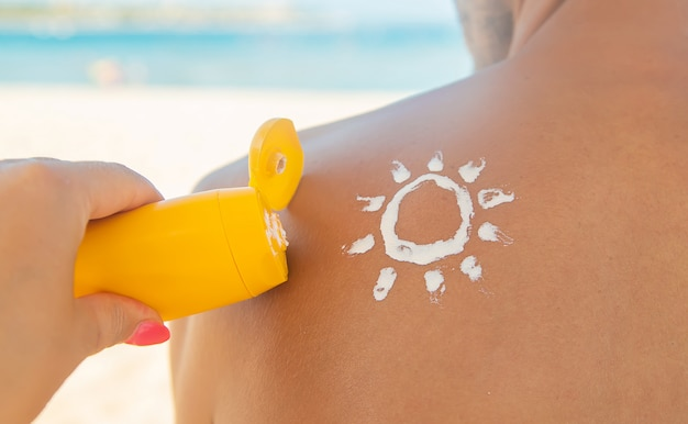 Het meisje op het strand brengt zonnebrandcrème aan op de huid van een man