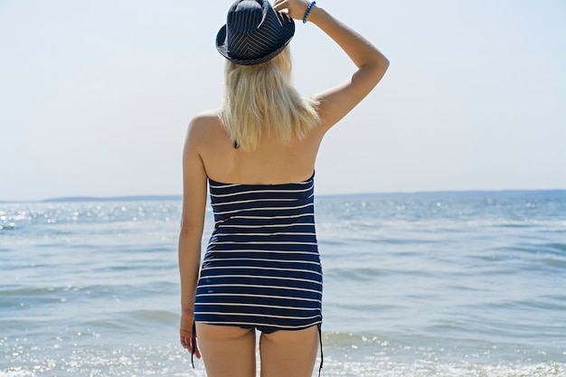 Het meisje op het strand in een zwempak en hoed kijkt naar de zee, het concept van vrije tijd. zee, strand, zomer. tijd ontspannen.