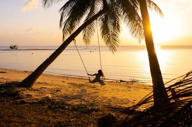 Het meisje op het strand rijdt op schommel tijdens zonsondergang. zonsondergang in de tropen, genietend van de natuur. swing vastgebonden aan een palmboom door de oceaan