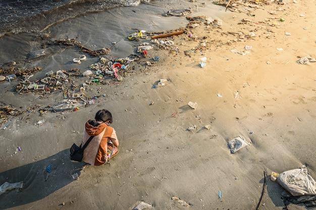 Het meisje op het vuile strand met zonsonderganglicht