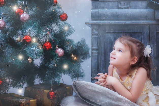 Het meisje op hoofdkussen kijkt zorgvuldig uit venster van kerstboom