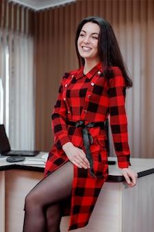 Het meisje op kantoor in een rode jurk
