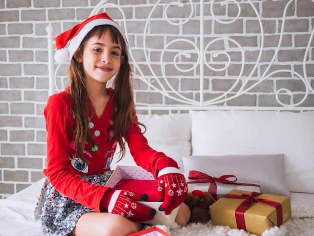 Het meisje opent de geschenkdoos op eerste kerstdag
