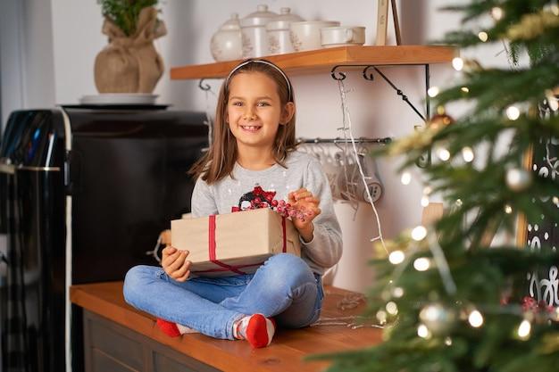 Het meisje opent een doos met een kerstcadeau van de kerstman