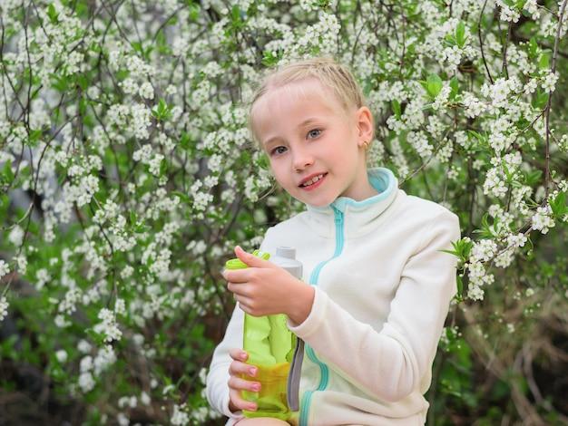 Het meisje opent een fles verfrissend drankje in het voorjaar bos