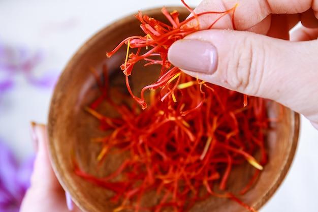 Het meisje pakt de saffraan van een houten bord. verse saffraan meeldraden. scheiding van de saffraandraadjes van de rest van de bloem.
