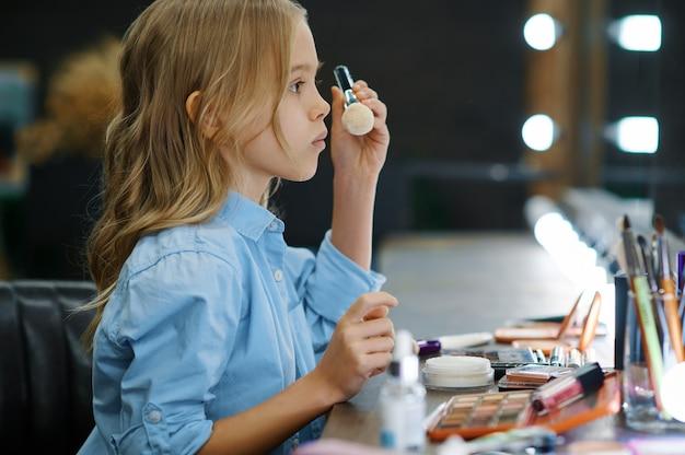 Het meisje past poeder toe bij de spiegel in de make-up salon