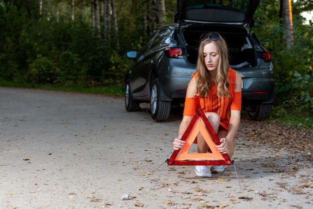 Het meisje plaatst een driehoek in rug van gebroken auto