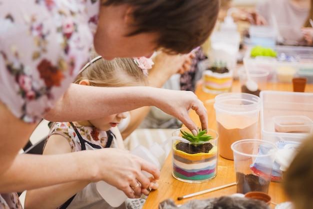 Het meisje plant een glasvorm, plant bloemen, glazen terarium