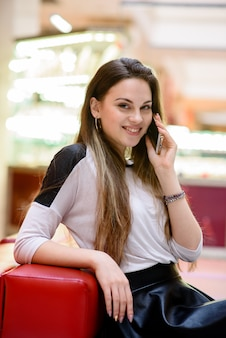 Het meisje praat aan de telefoon in het winkelcentrum.