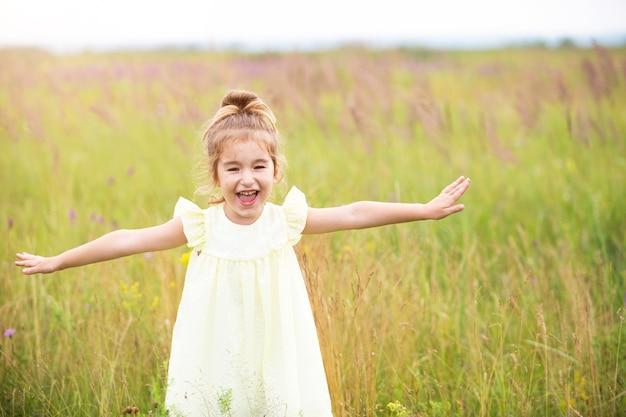 Het meisje rent het veld in met haar armen gestrekt als een vliegtuig. zorgeloze jeugd, zomer vrijheid, reizen. internationale kinderdag. muggenspray, cottage core.